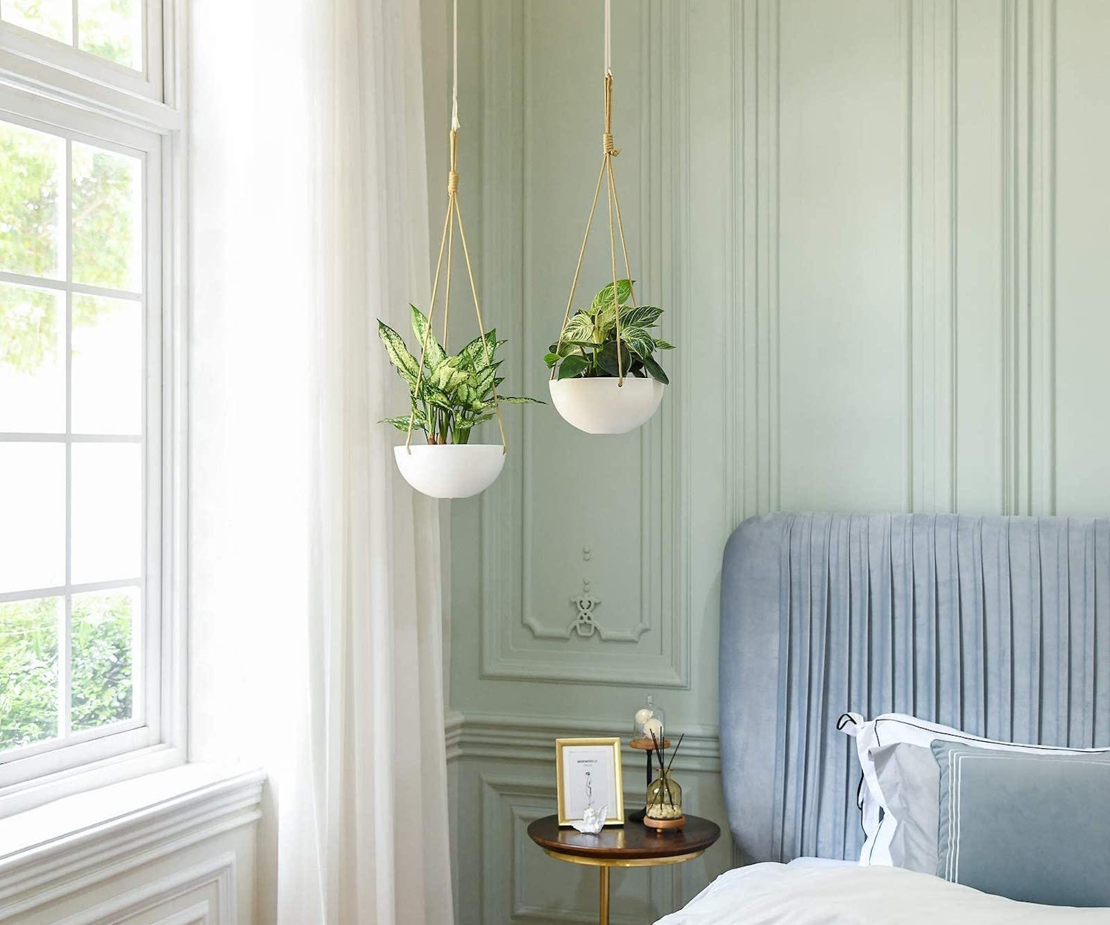 Two of the Mkono Ceramic Planters hanging in the corner of a bedroom.