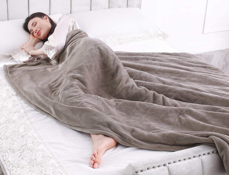 Woman sleeping under a grey, fluffy, heated blanket .