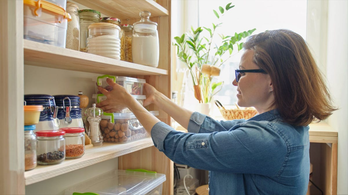 A woman stacking clear storage containers of food in a pantry.