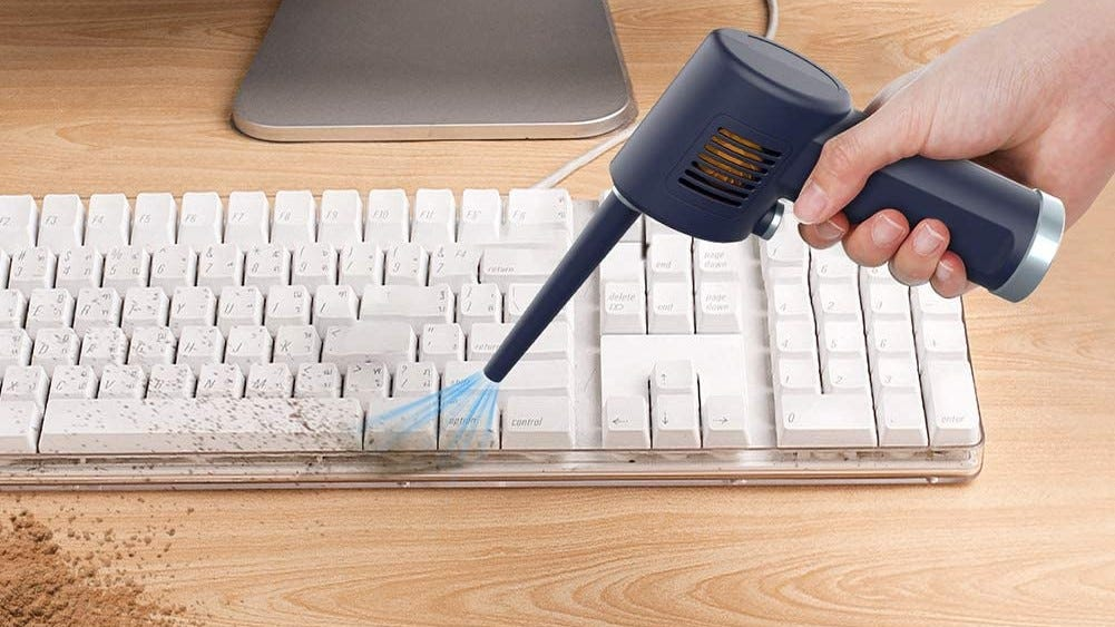 Electric air duster being used to clean dust from a keyboard.
