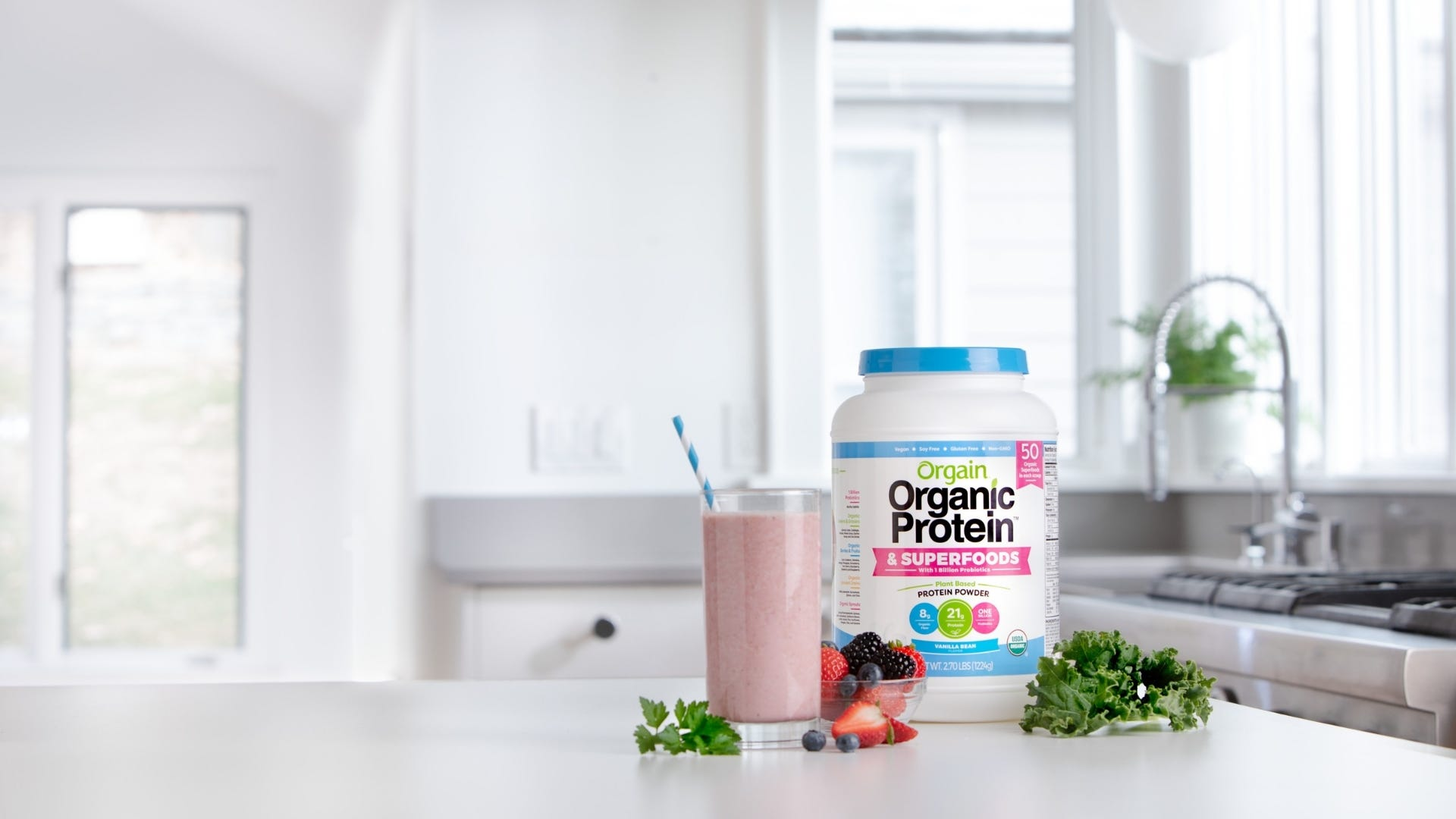 A container of Orgain Organic Protein and Superfoods next to a smoothie, leafy greens, strawberries, and blueberries.