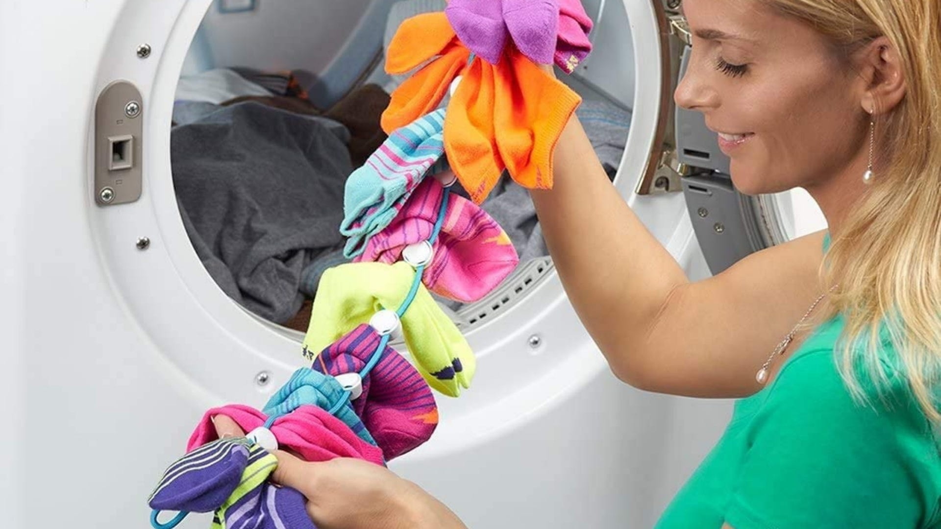 A woman holding a SockDock with a bunch of socks attached to it.