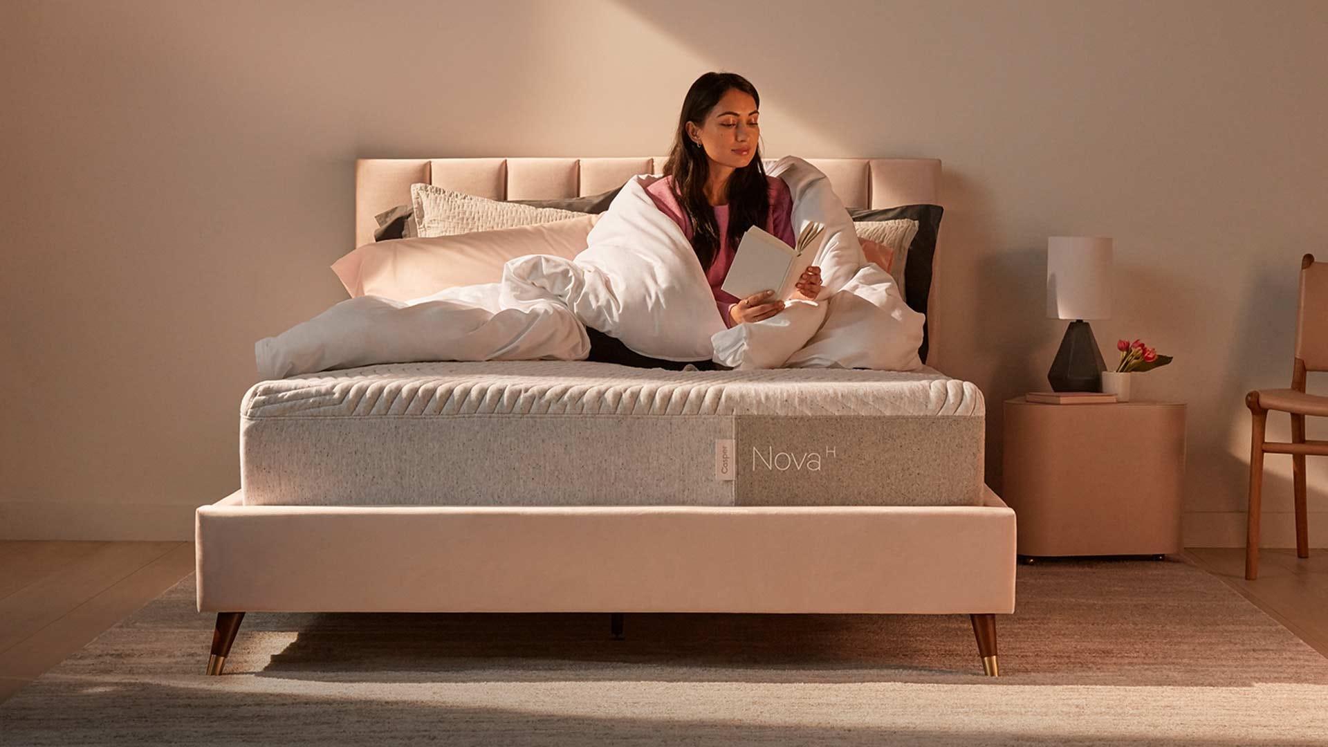 A woman sitting on a Casper hybrid mattress.