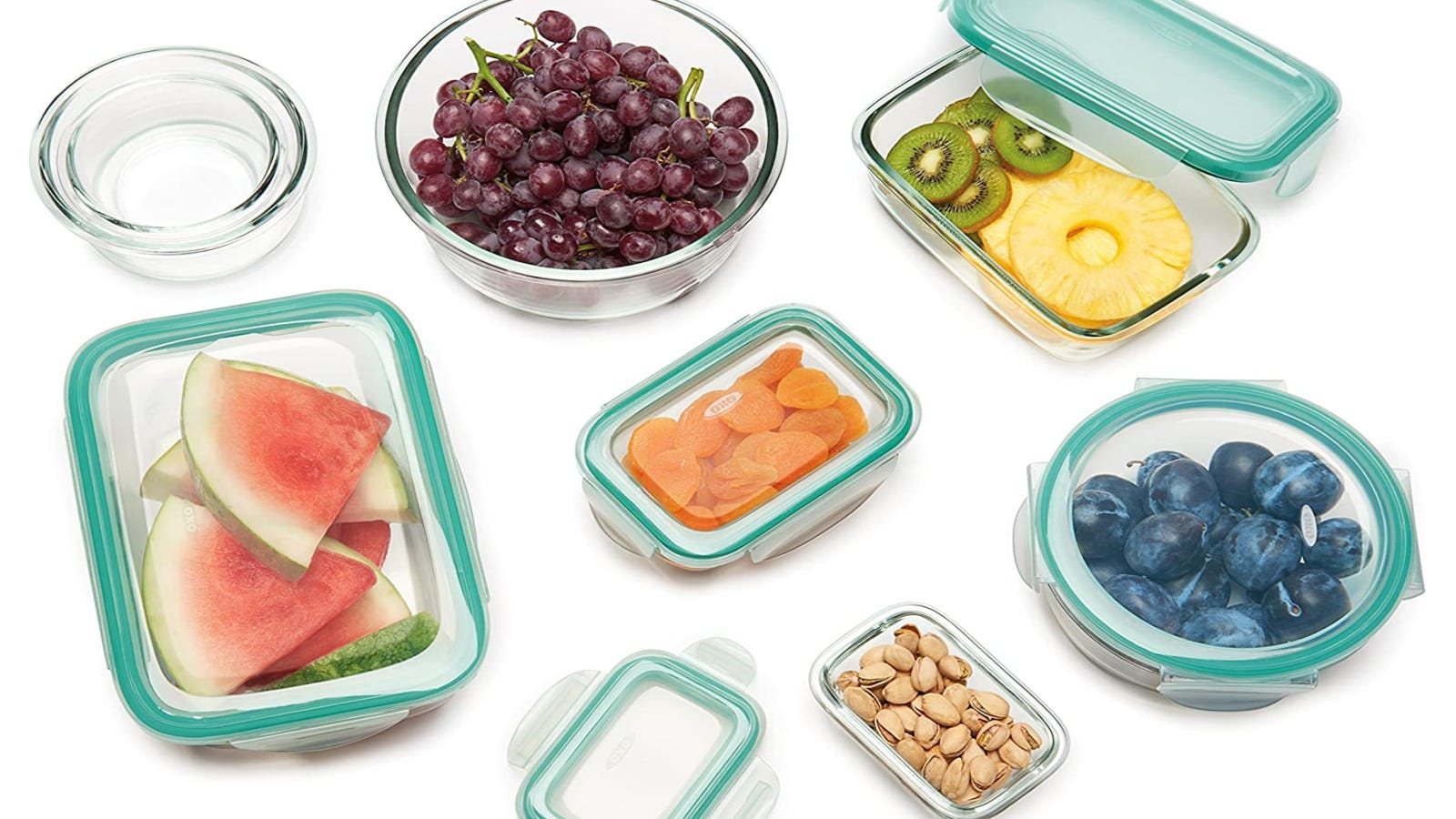 An assortment of OXO glass food storage containers filled with various foods on a white background.