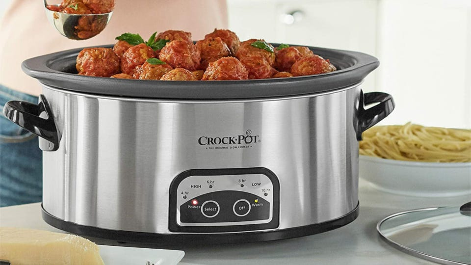 A Crock-Pot filled with Italian meatballs, and a bowl of spaghetti on the side.