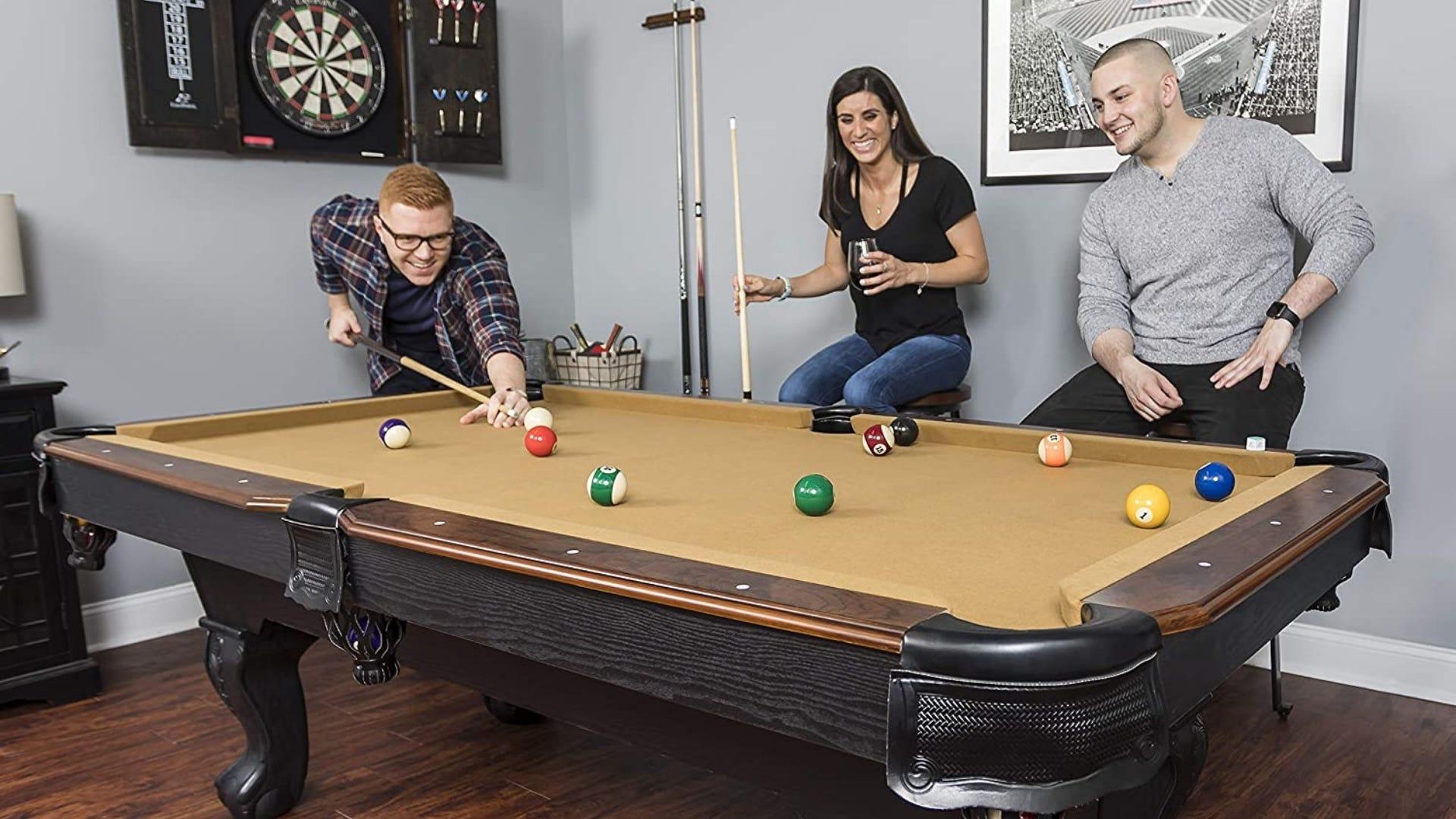 Three friends playing pool.