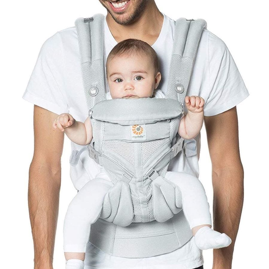 A man carrying a baby in front in the ErgoBaby Omni 360 carrier.
