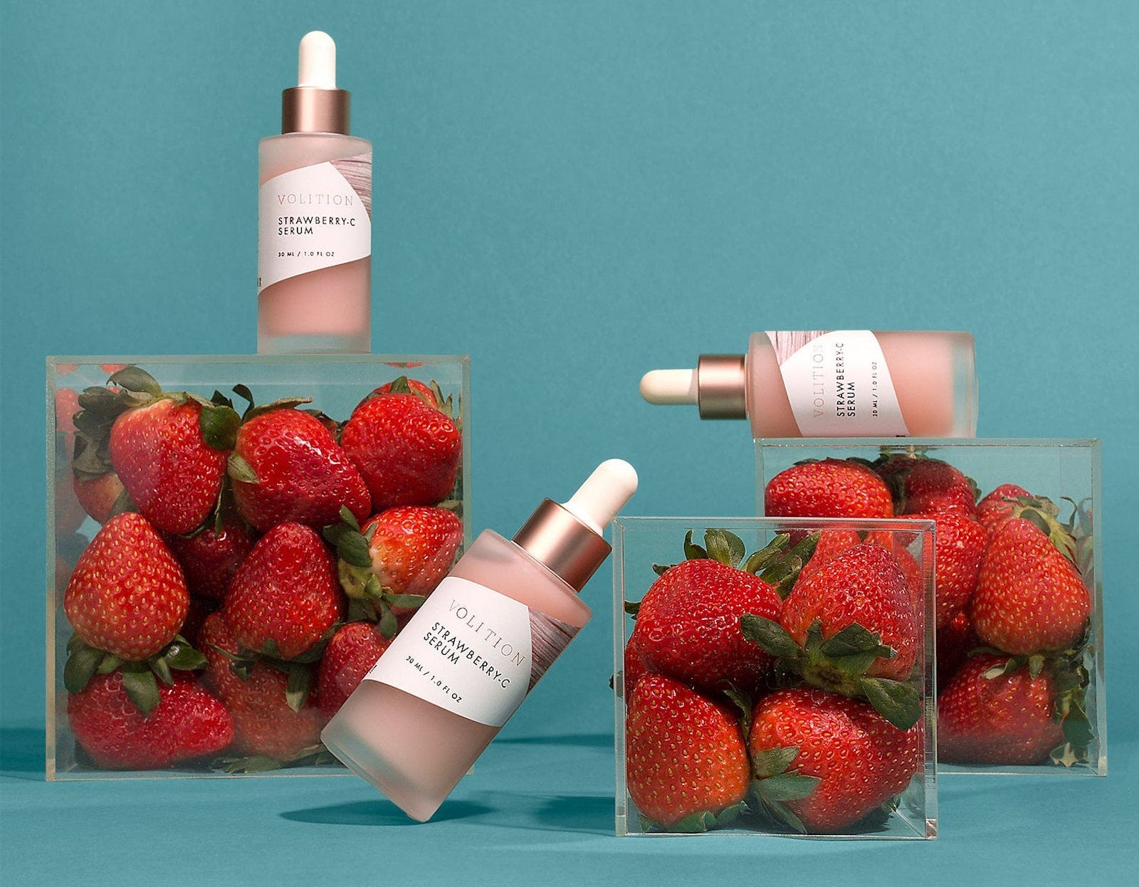 Glass boxes of strawberries with glass dropper-top bottles of a pink serum sitting on top