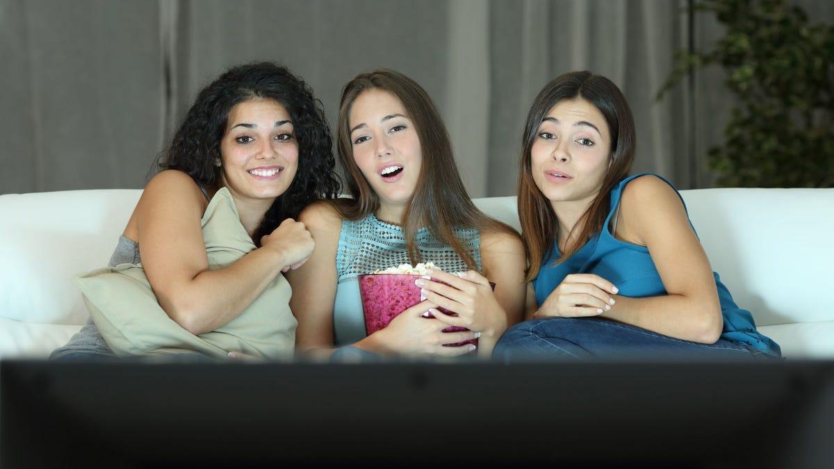 Three women watching a rom-com on the Hallmark Channel.