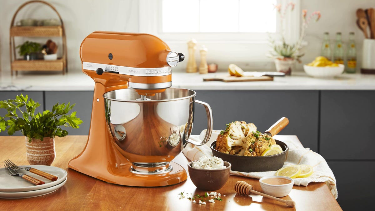 A KitchenAid mixer sits on a countertop surrounded by ingredients.