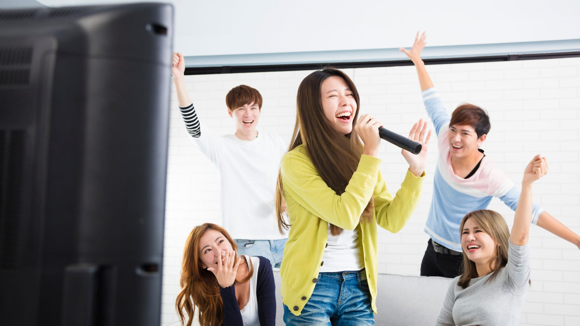 A woman holds a mic up to her face as she sings karaoke with her friends dancing around her.