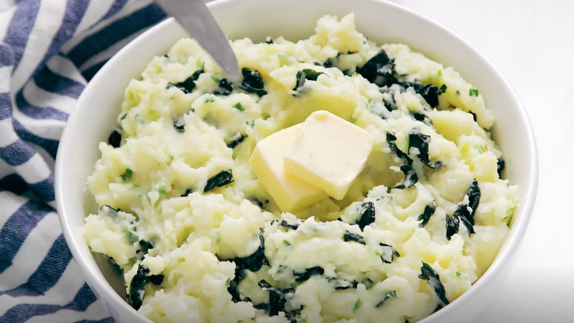Bowl of mashed potatoes mixed with greens.