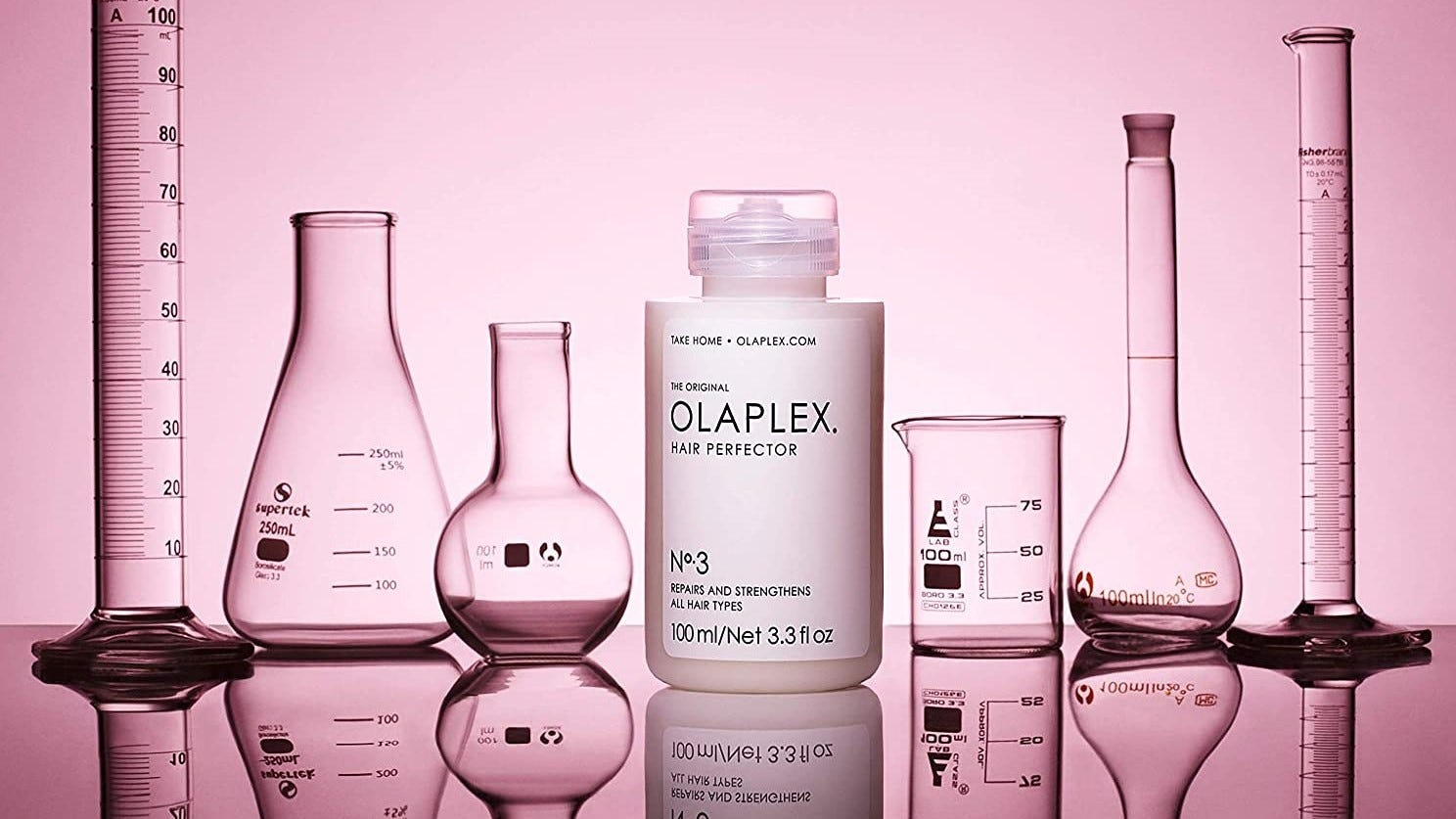A bottle of Olaplex Hair Perfector No. 3 surrounded by beakers and and measuring tubes.