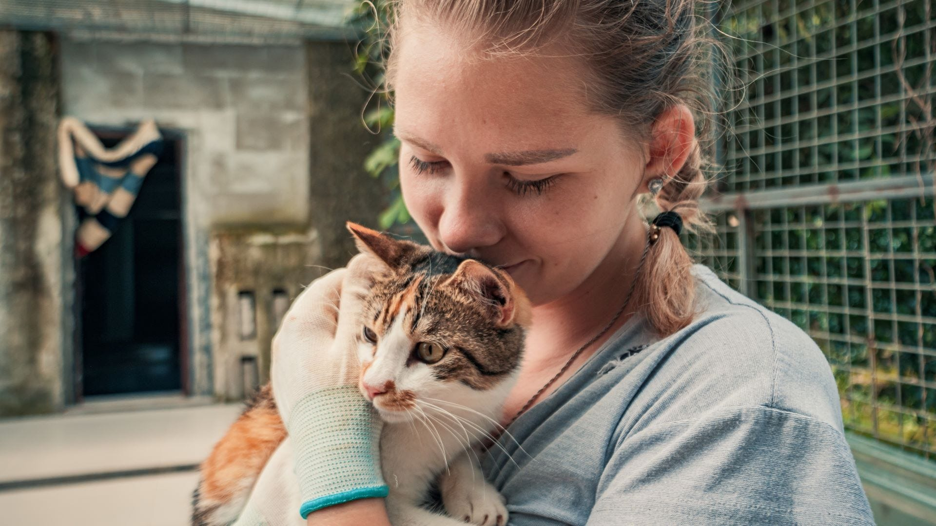 A young girl at an animal shelter holding a cat.