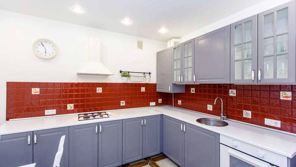 A gray and white kitchen with a red tile backsplash.