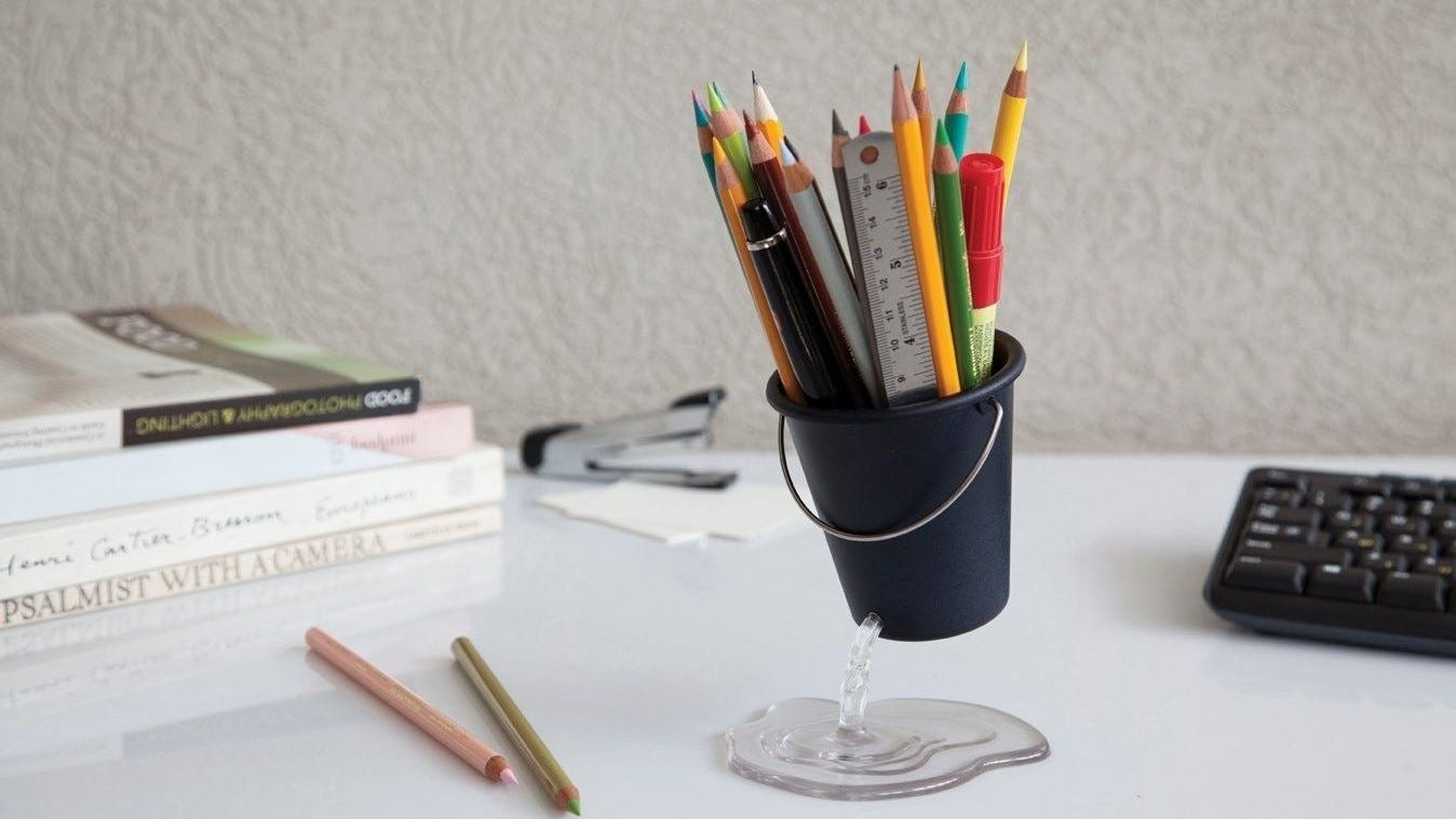 Leaky bucket pencil holder on a desk.
