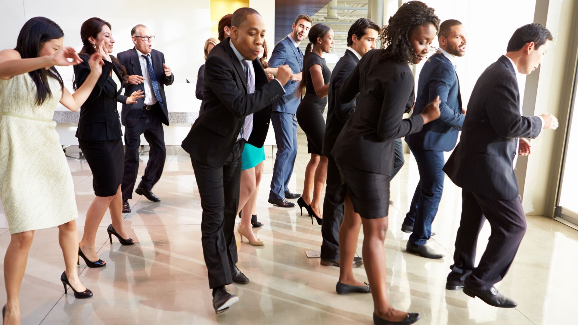 A group of people line dancing at an office.