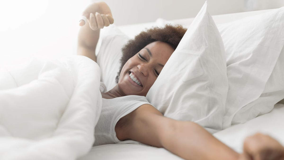 A woman in bed waking up and stretching with a smile.