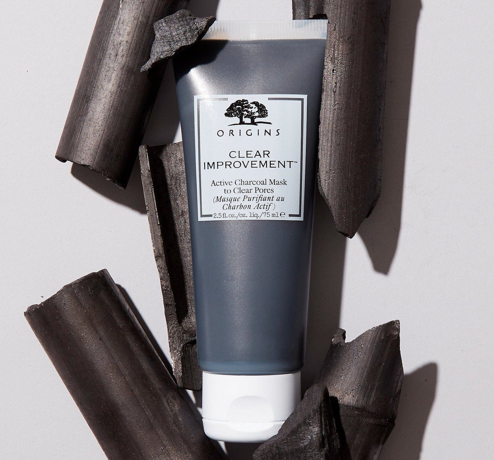 A tube of black charcoal paste surrounded by tubular pieces of charcoal