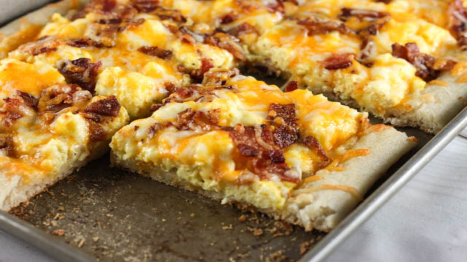 A sheet pan of breakfast pizza topped with scrambled eggs, bacon, and cheese.