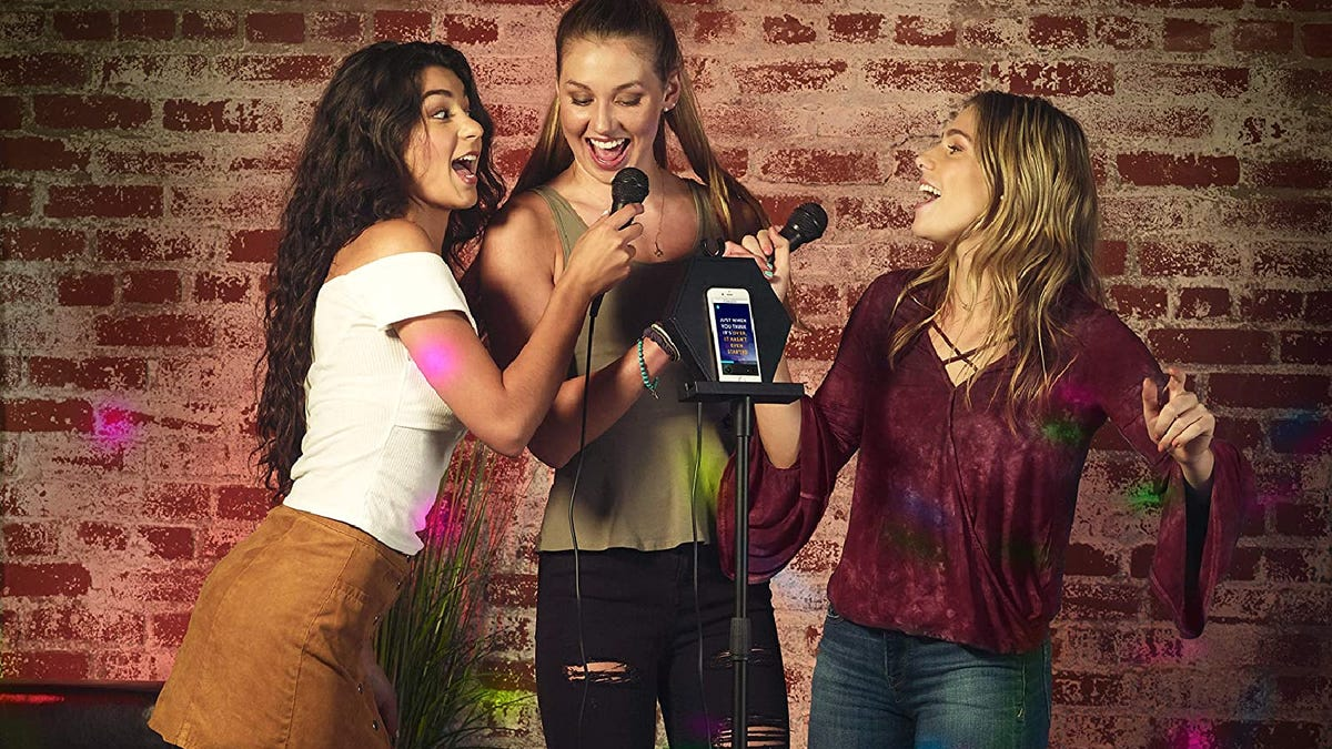 Three female friends sing and smile next to a karaoke machine.