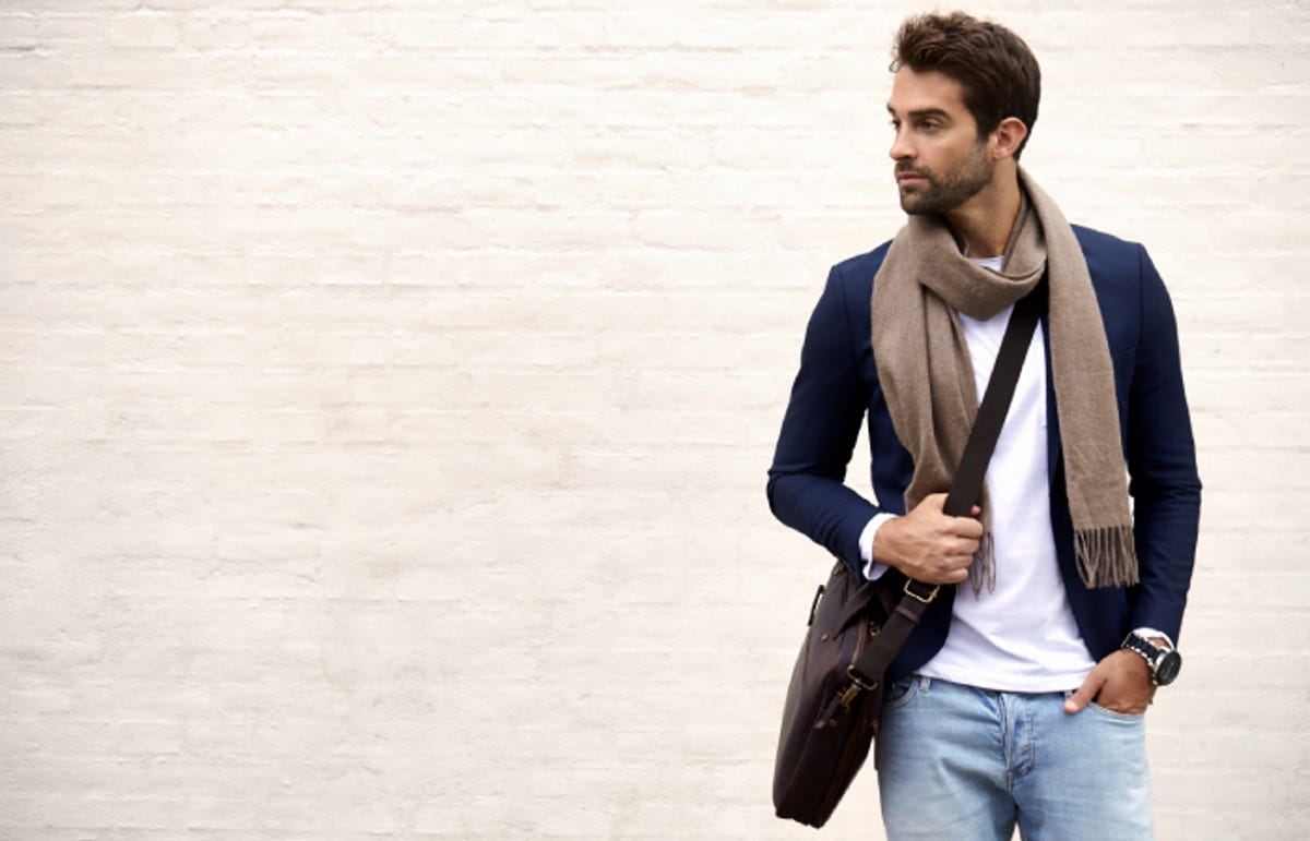 an attractive man with a scarf and cross-body bag looking to the side