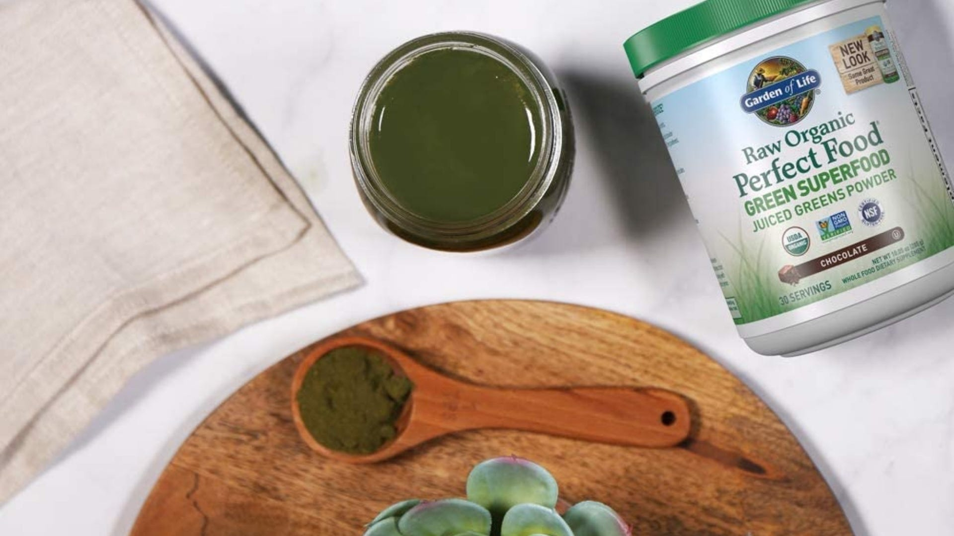 A bottle of Garden of Life Raw Organic Greens on a table next to a green smoothie.