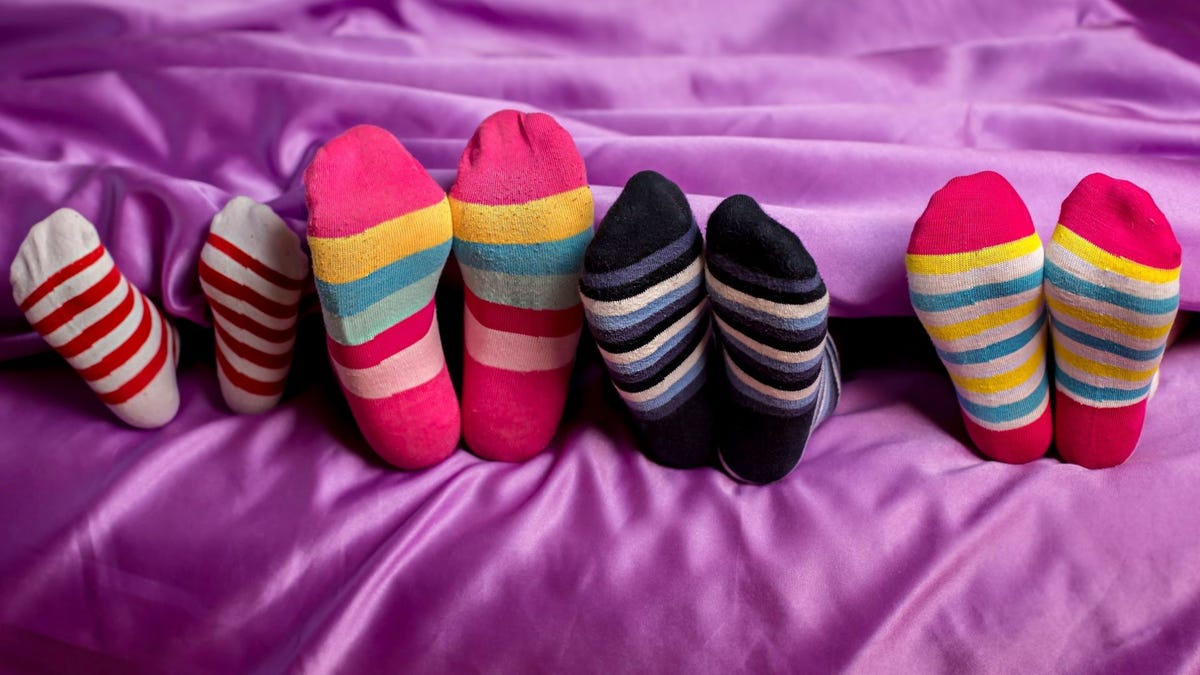 Four pairs of feet in bed wearing striped socks.