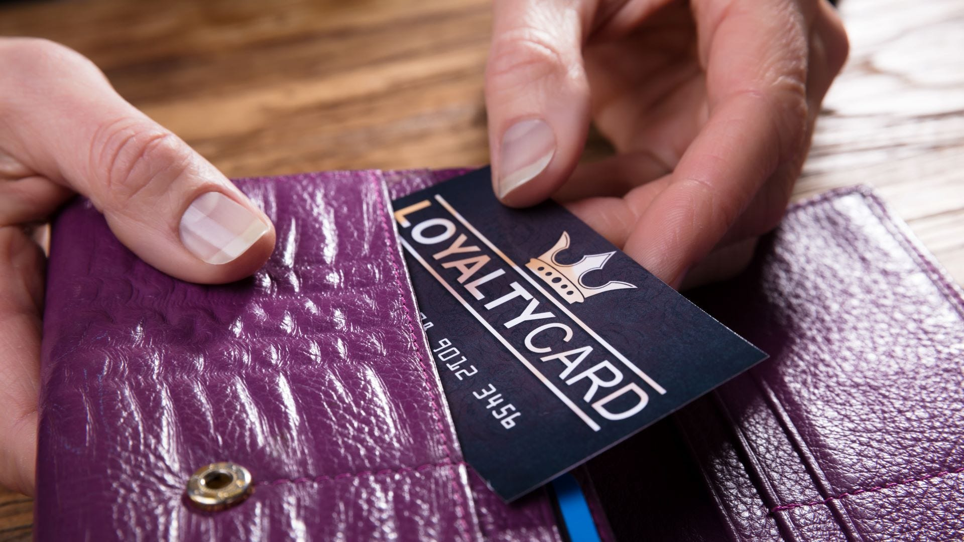 Someone removing a loyalty card from a wallet.