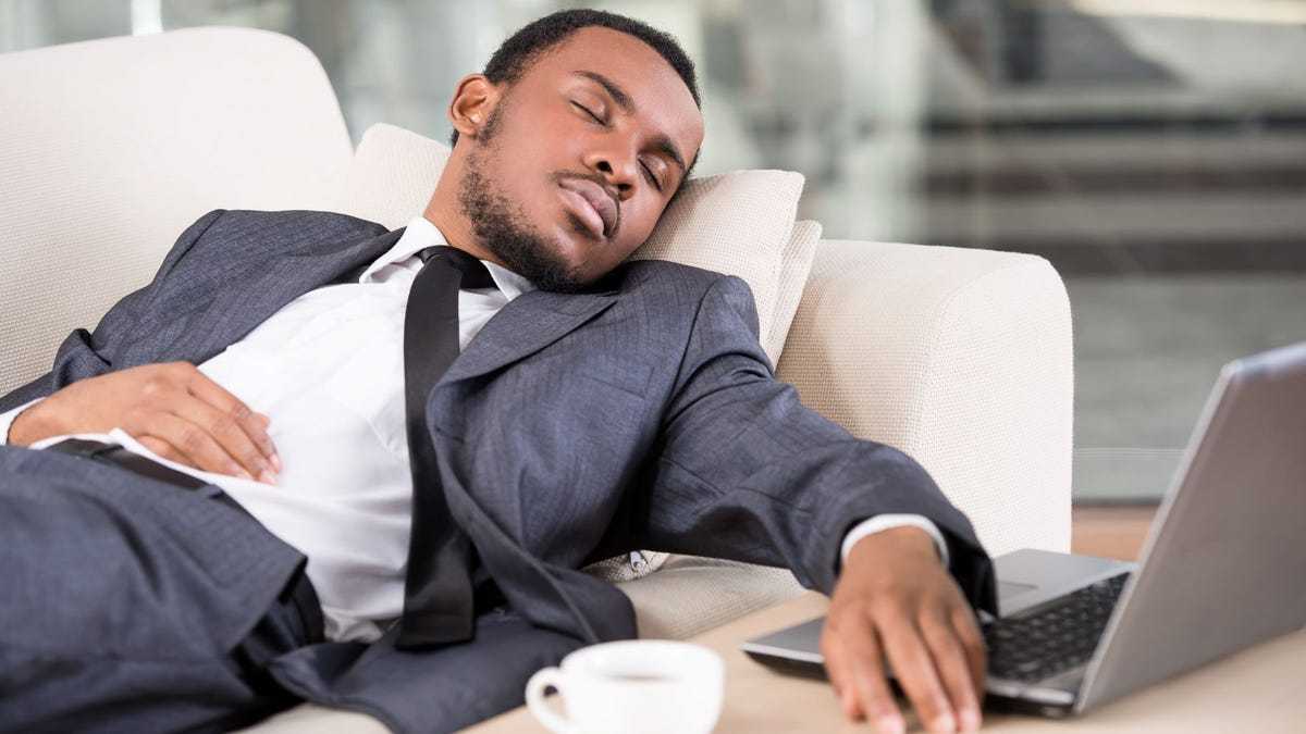 A young man wearing a suit, napping on a sofa next to a laptop.