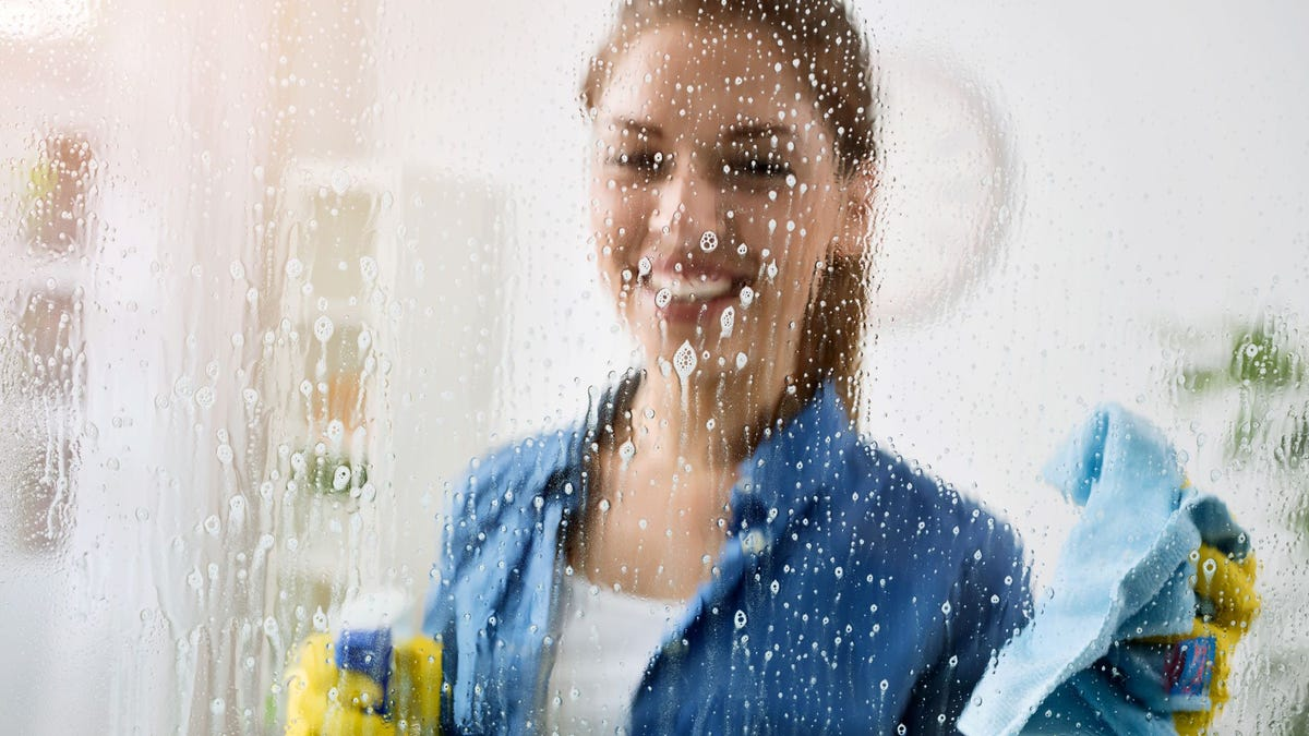 A window soaked with cleaner and a woman on the other side holding a bottle of cleaner and a microfiber cloth.