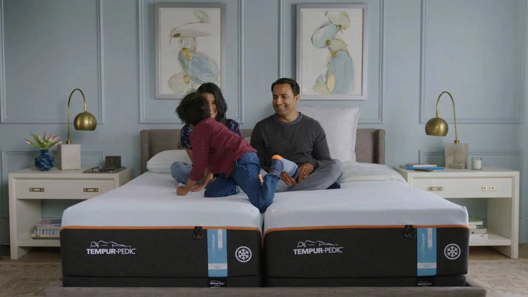 A family sitting on a Tempur-Pedic bed.