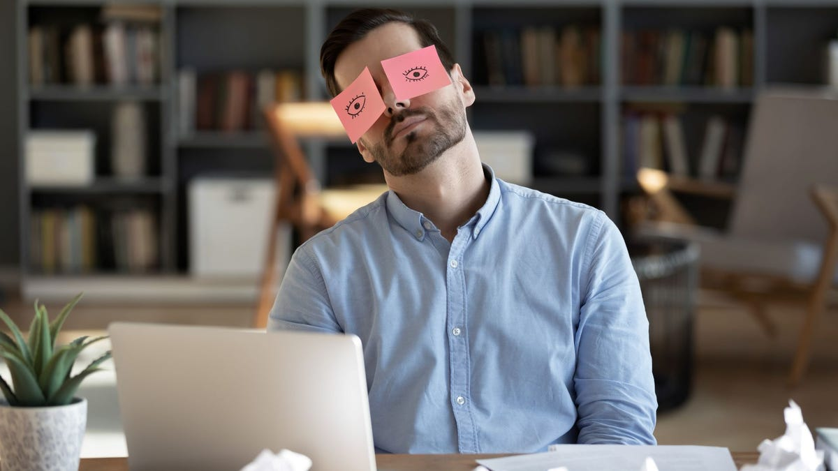A man at a desk with two Post-Its of hand-drawn eyes over his eyes.