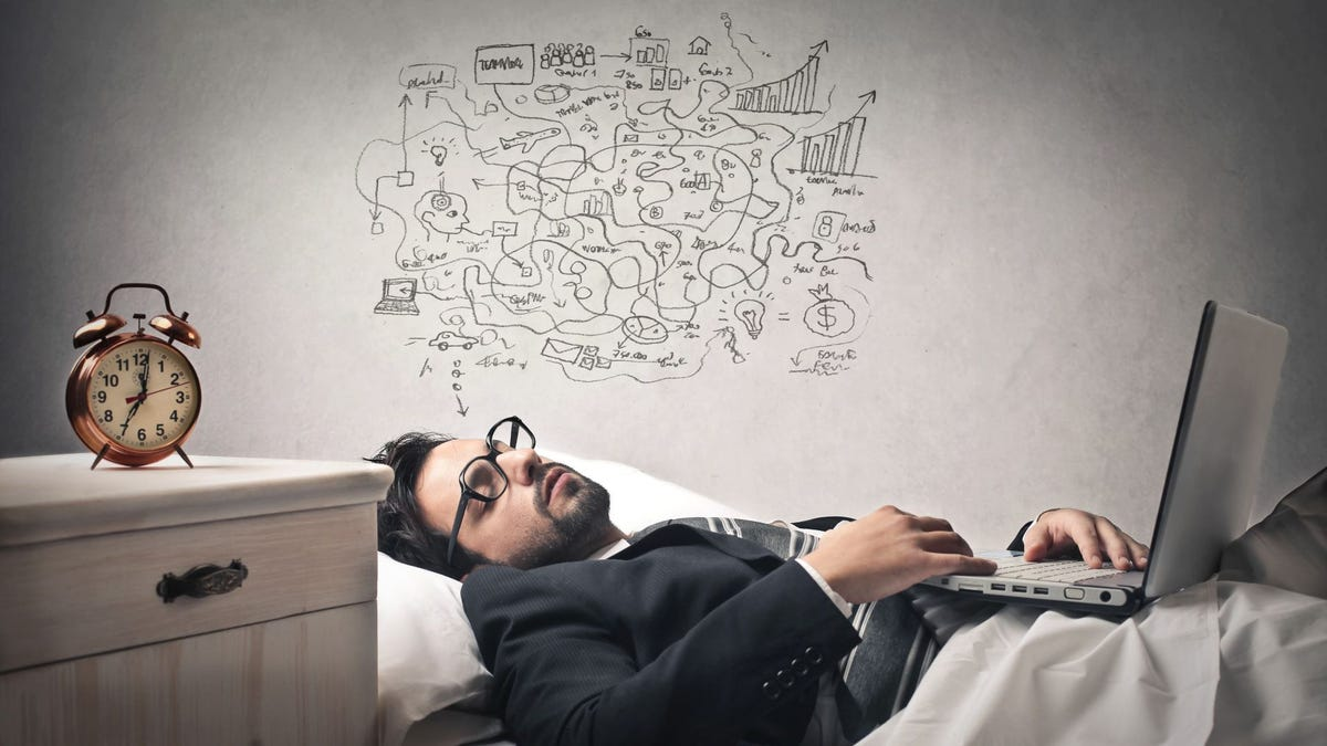 A man asleep in bed with his laptop open and a crazy maze of drawings above his head to indicate a crazy dream.