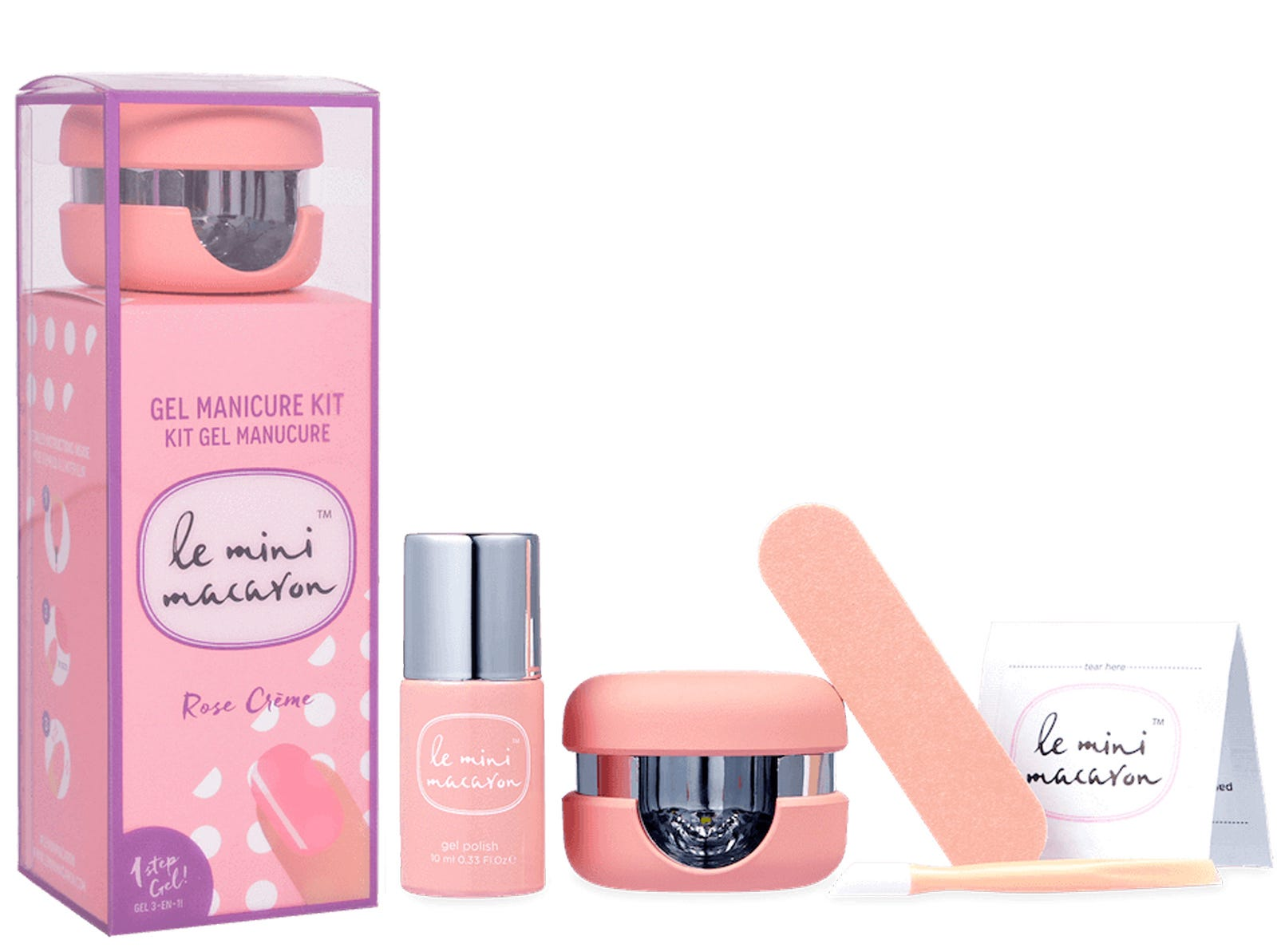 A kit with a pink box, a bottle of light pink nail polish, a nail file, and a small round manicure lamp