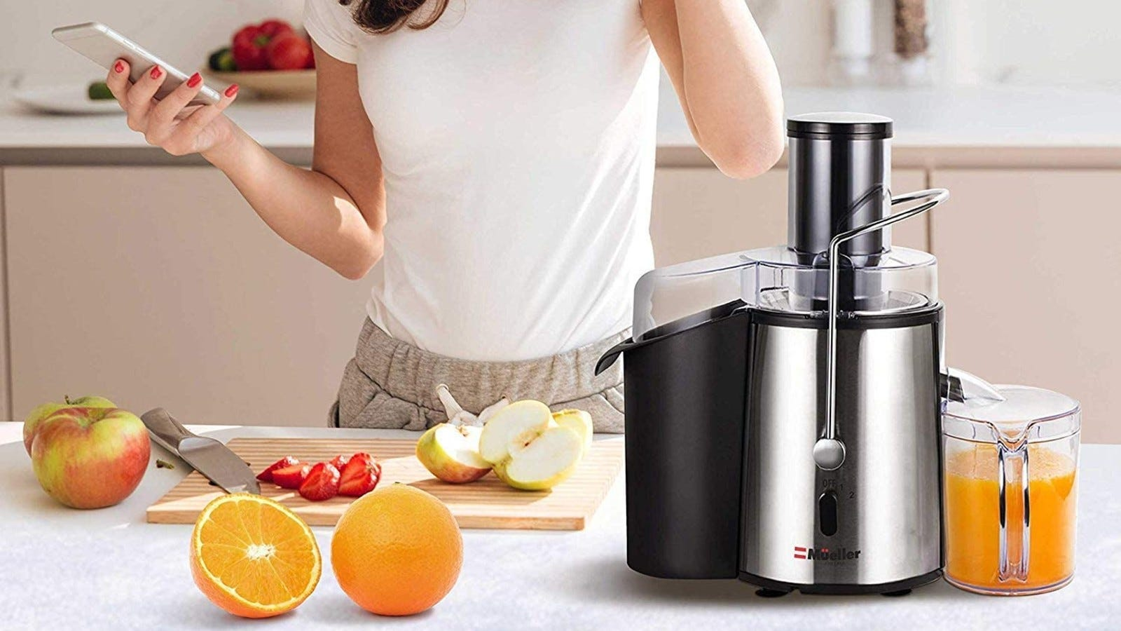 juicer on counter with oranges