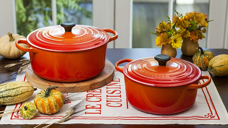 Two orange Le Creuset Dutch ovens, placed on a table with gourds and fall flowers and decorations around.