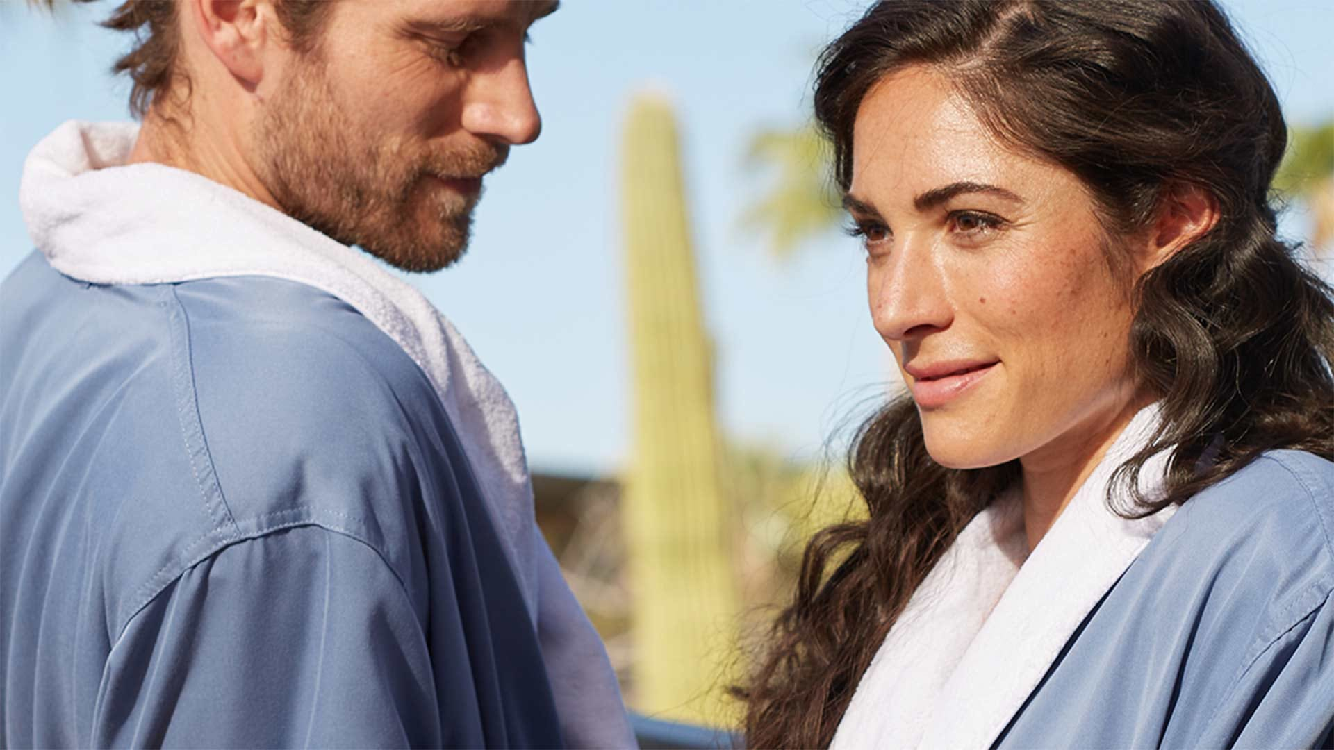 Man and woman in matching blue robes.