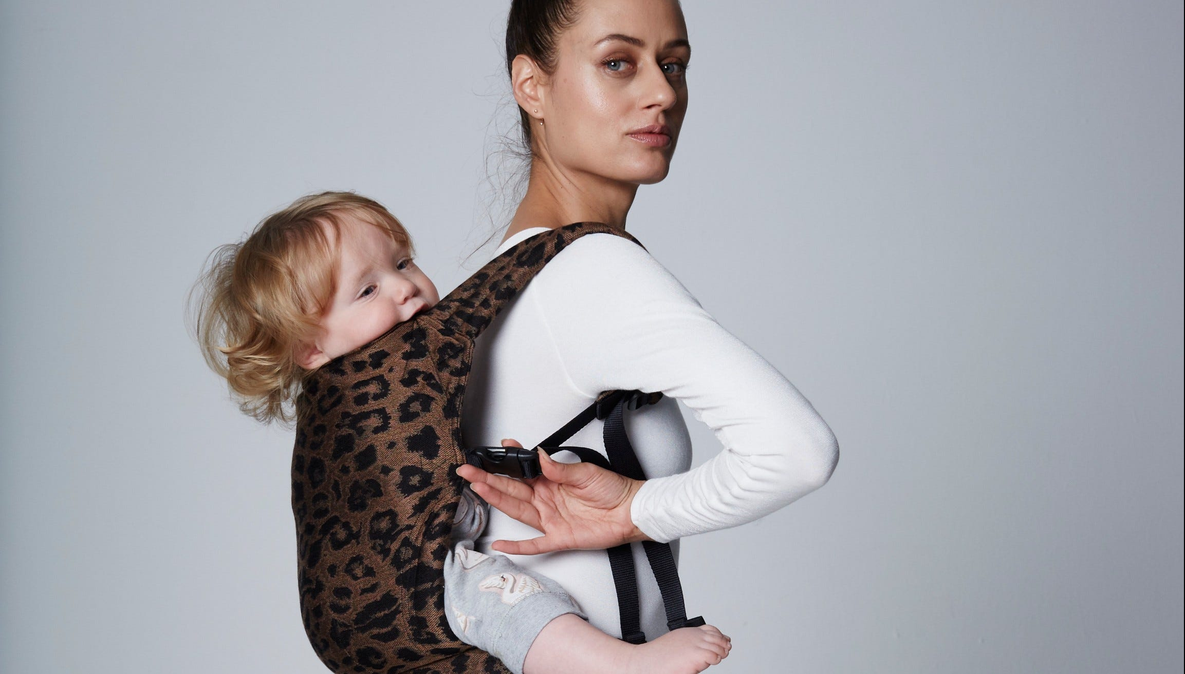A woman carrying baby in the Artipope Zeitgeist carrier.