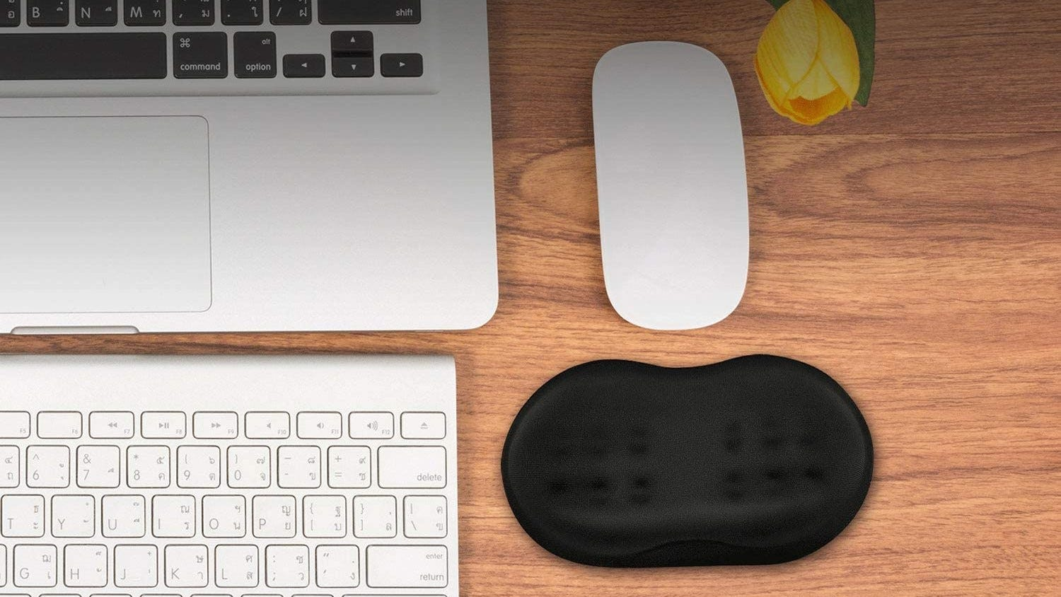 The Vankey wrist pad on a desk next to a computer.