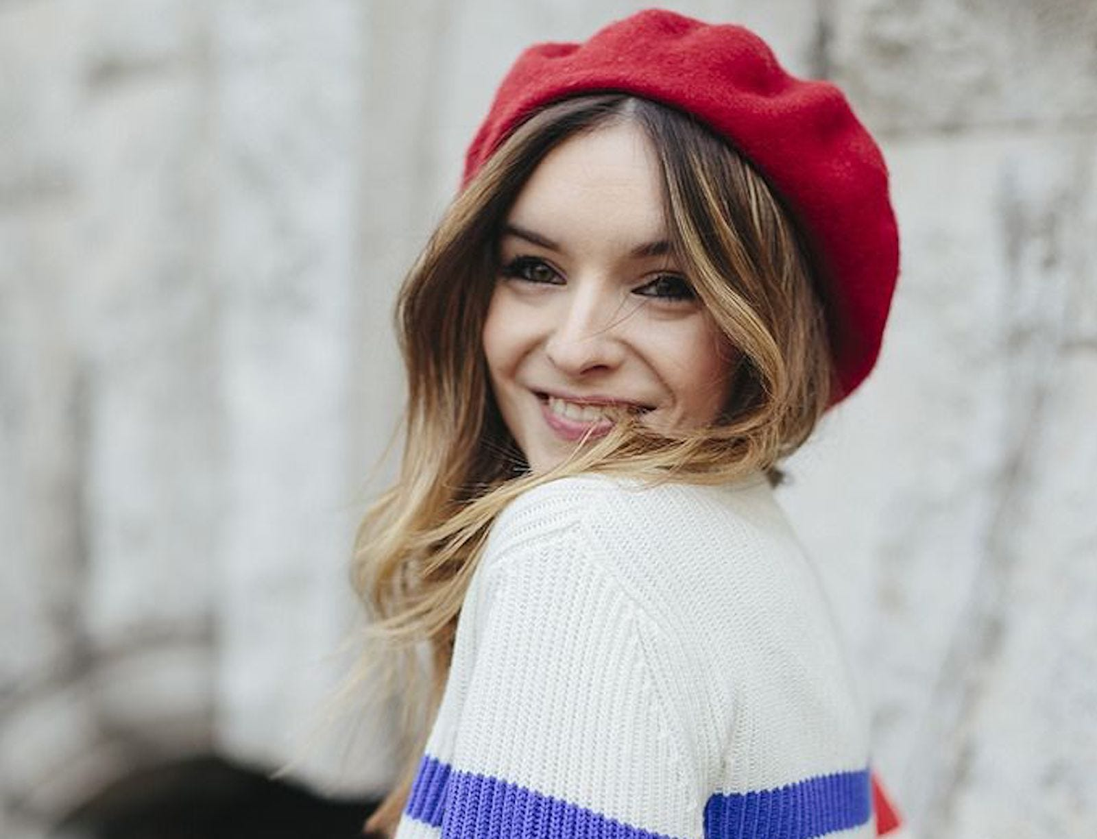 A woman wearing a white sweater with a blue stripe and a red wool beret