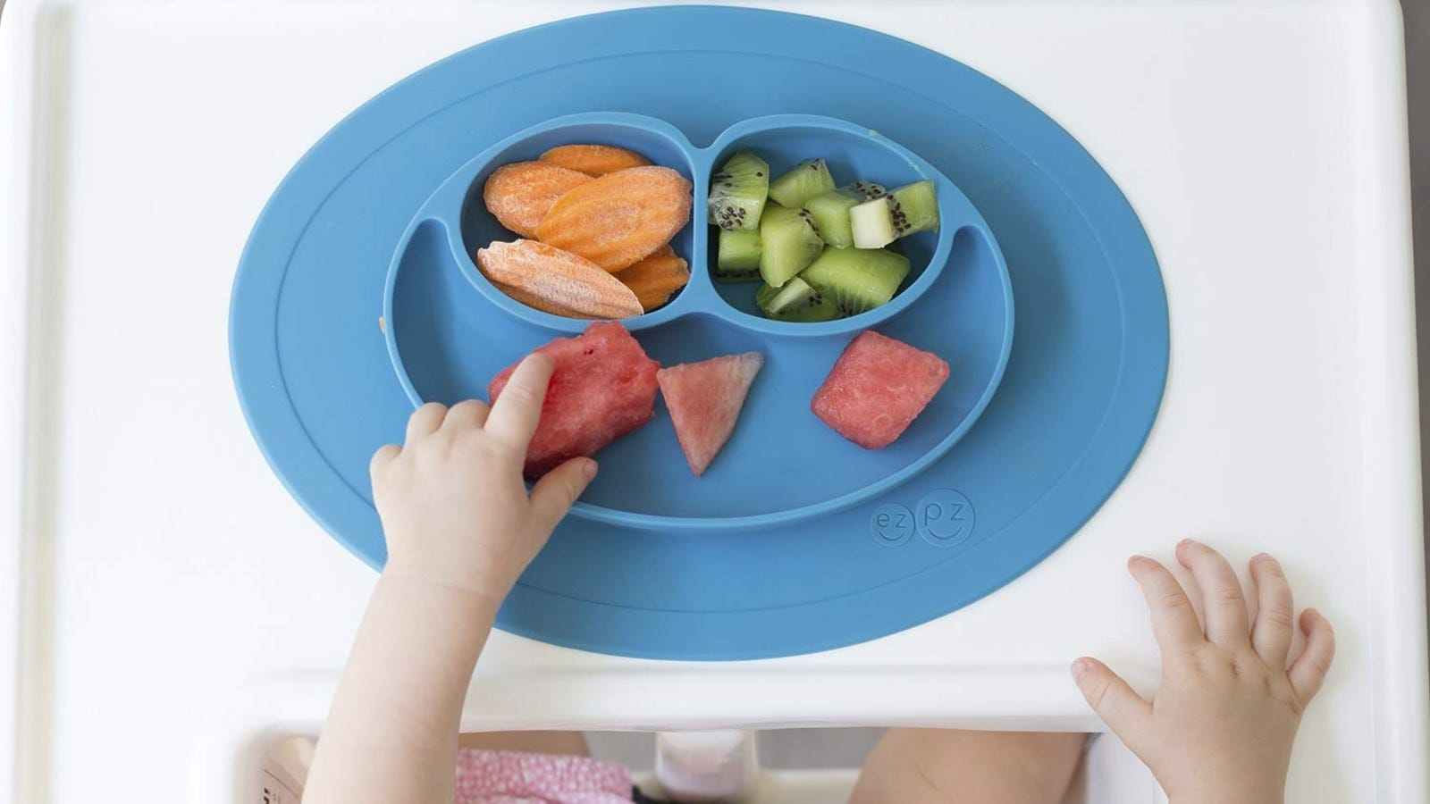 A toddler eating fruit and veggies from the blue ezpz Mini Mat.
