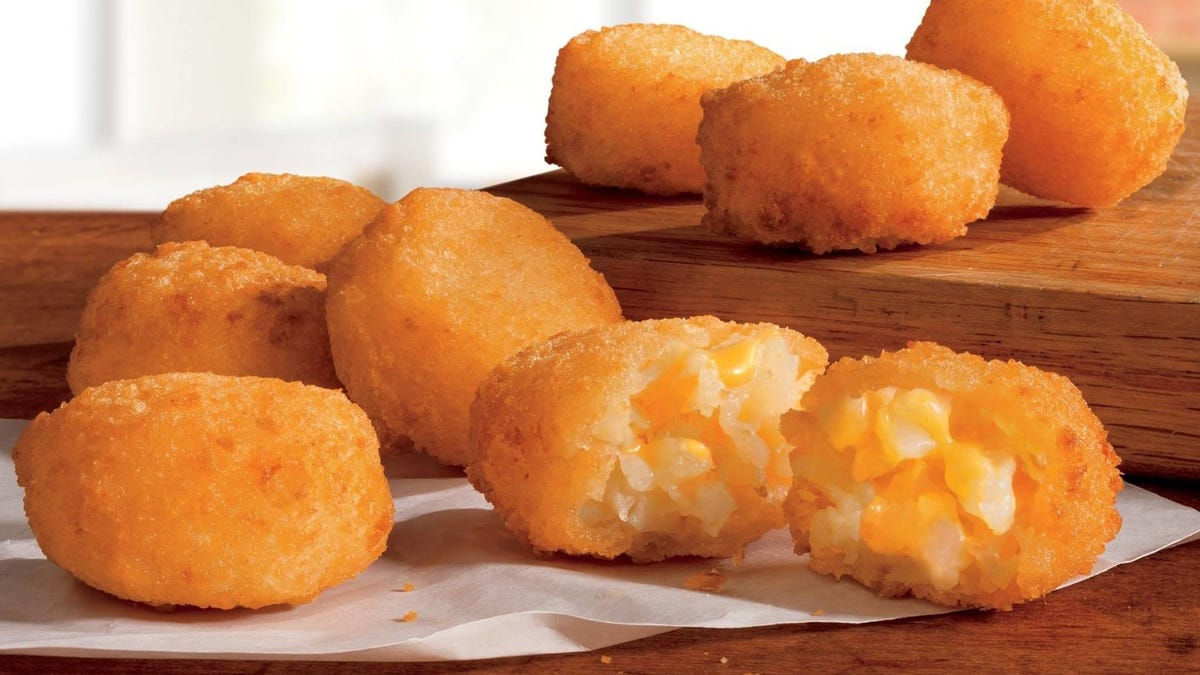 Eight of Burger King's Cheesy Tots sitting on a wrapper.