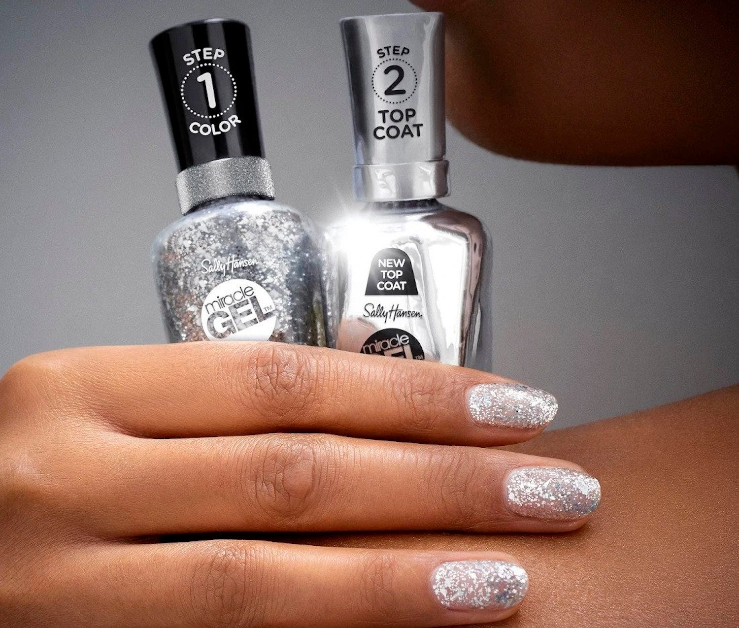 A dark-skinned hand with silver nails holding two nail polish bottles