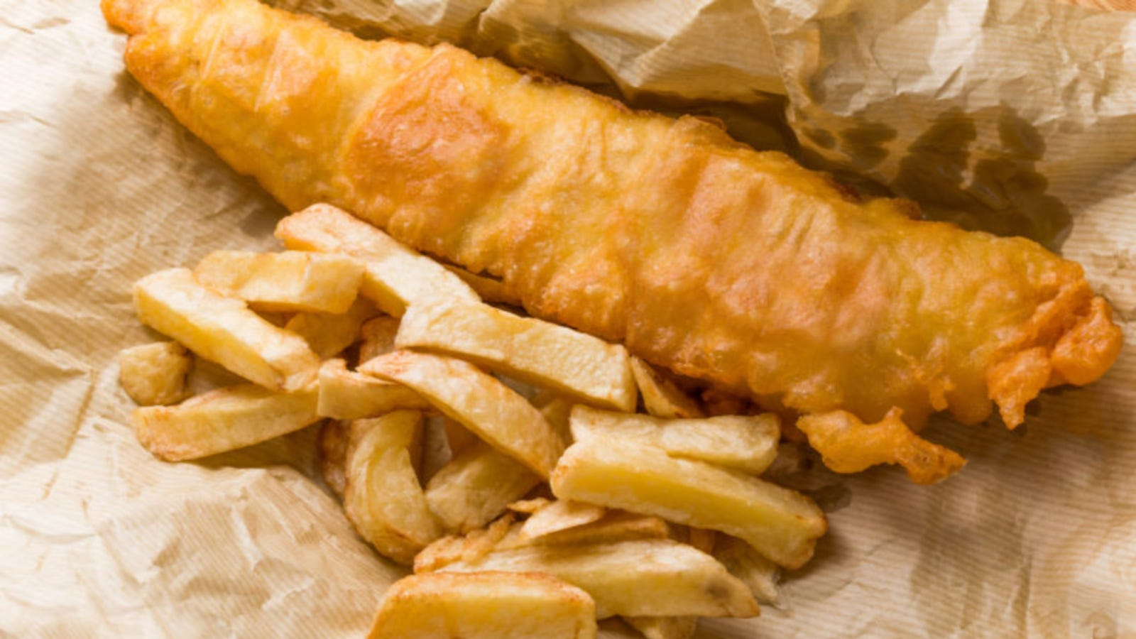 Fish and chips on brown parchment paper.