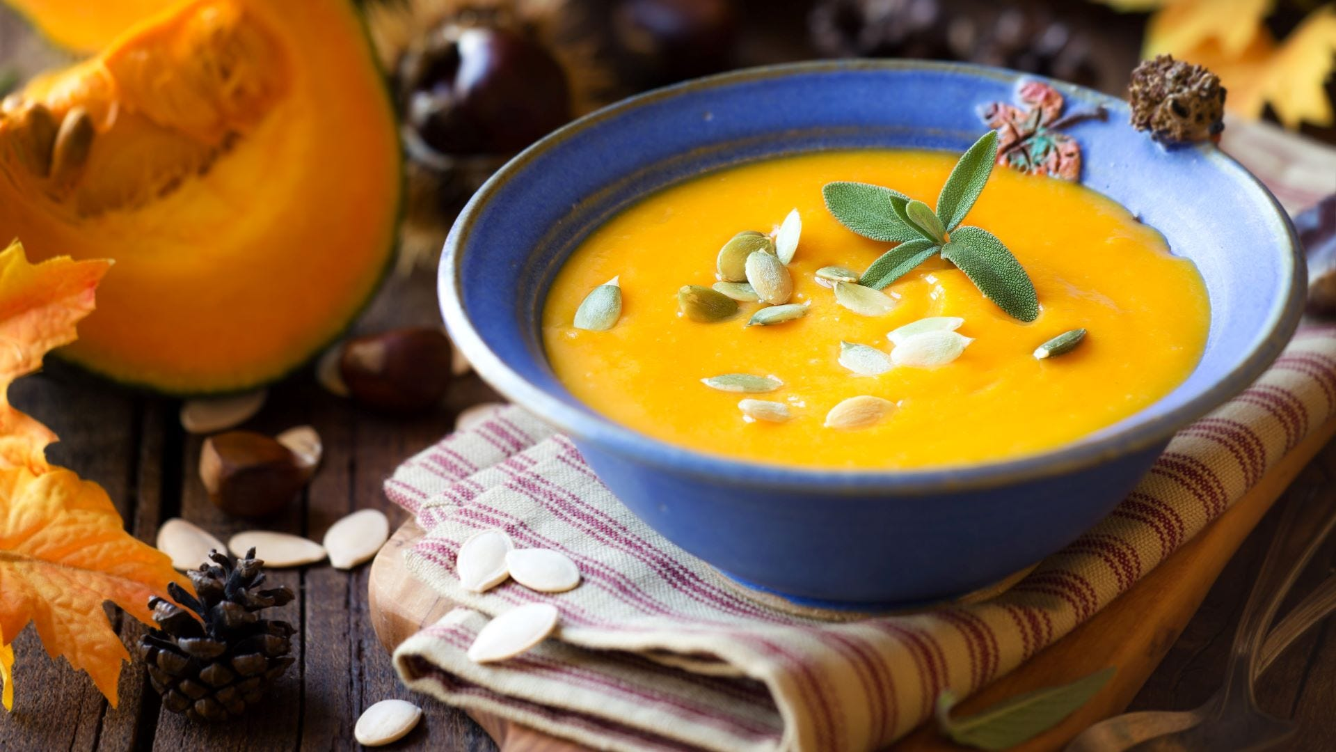 A bowl of pumpkin and sage soup with pumpkin seeds on top.