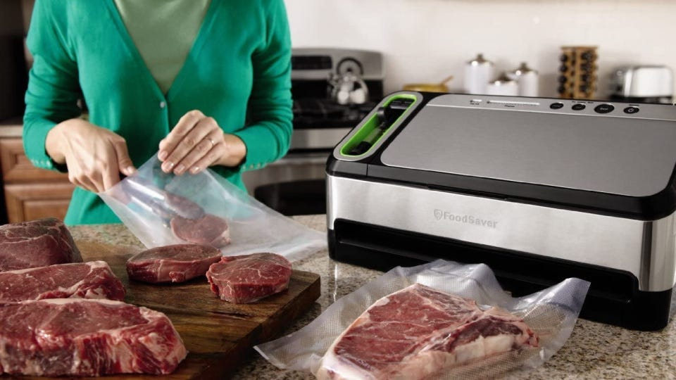 A woman placing various steaks in sealer bags, getting read to vacuum seal multiple cuts of beef, with a FoodSaver 2-in-1 on the counter next to her.