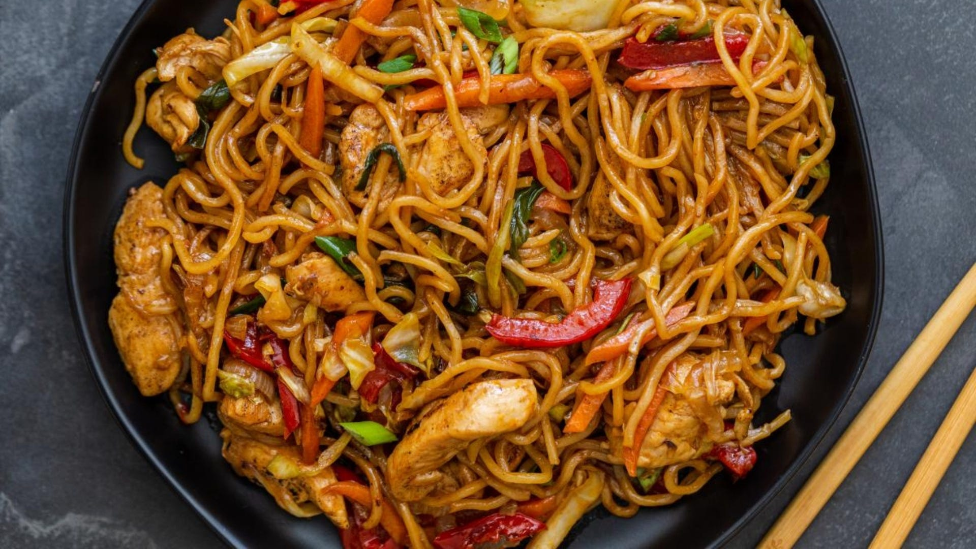 plate of yakisoba noodles, chicken, and vegetables