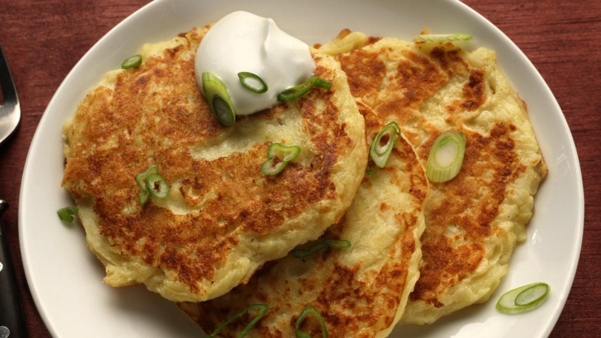 Potato pancakes on a plate, topped with sour cream and chives.