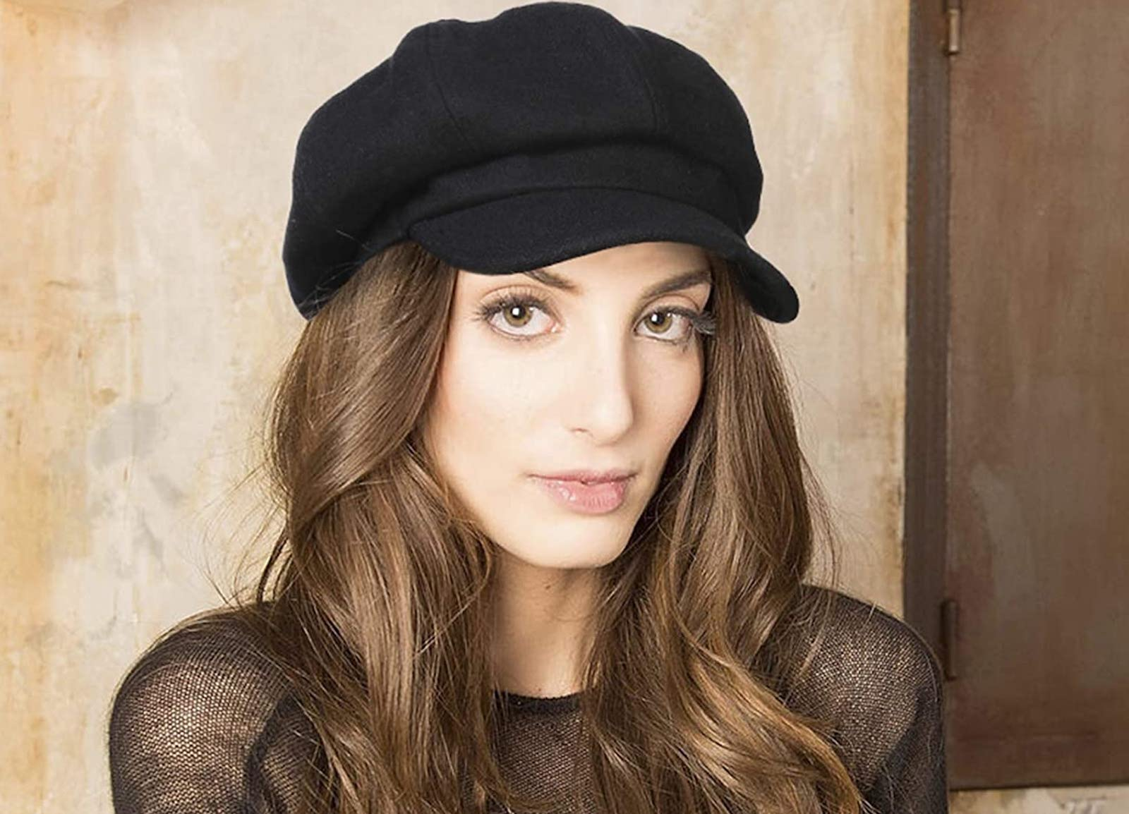 A brunette woman wearing a black newsboy cap against a brown wall